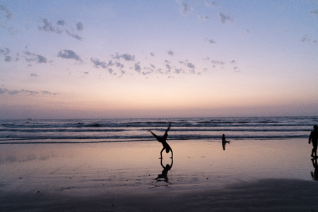 On a hot summer evening youth performs somersaults, flips  handstands at  beach. Silhouetted at dusk with clouds in  sky.