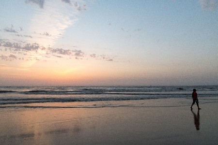 A youngster taking a walk on  beach,  against a setting sun. Mumbai beaches are always popular in summer.