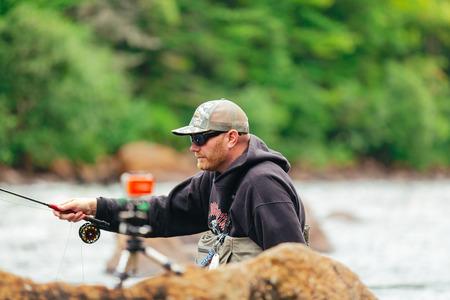 Man Fly fishing on Jacques-Cartier river  in Parc national de la Jacques-Cartier, Quebec. 免版税图像