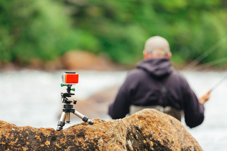 professional sports: Man Fly fishing on Jacques-Cartier river with go-pro, in Parc national de la Jacques-Cartier, Quebec.