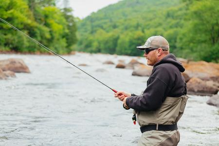 El hombre pesca con mosca en el río Jacques-Cartier, en Parc national de la Jacques-Cartier, Quebec.