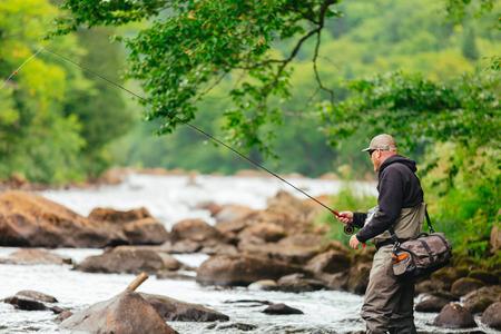 trucha: El hombre pesca con mosca en el río Jacques-Cartier, en Parc national de la Jacques-Cartier, Quebec.