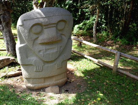 An ancient statue stands guard at a burial site at San Agustin archaeological park, Colombia Stock Photo