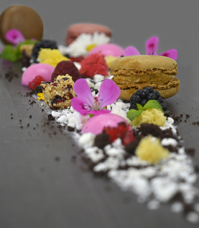 Presentation dessert, biscuit, fake caviar, molecular spheres, macarons, maltodextrin, chocolate, and edible flowers.