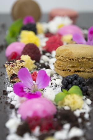 Presentation dessert, biscuit, fake caviar, molecular spheres, macarons, maltodextrin, chocolate, and edible flowers.
