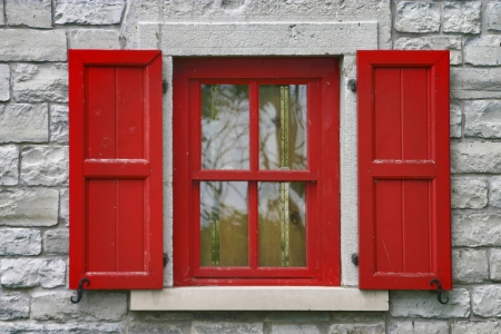 Rode vensterblinden, grijze steenmuur Stockfoto