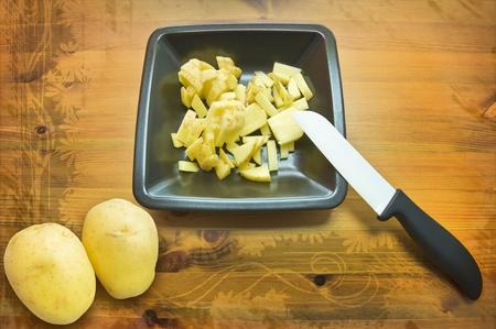 nutricion: Two whole  potatoes, cut potatoes on handmade ceramic plate with ceramic knife Stock Photo