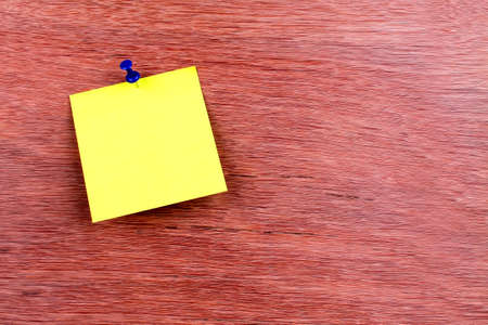 yellow reminder sticky note pin on wooden board, empty space for text