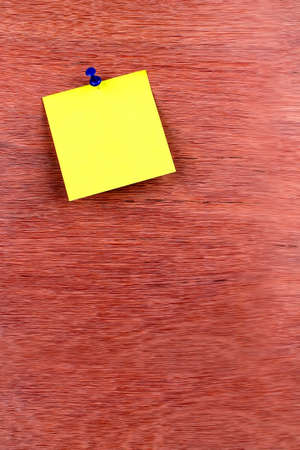 co cork: yellow reminder sticky note pin on wooden board, empty space for text