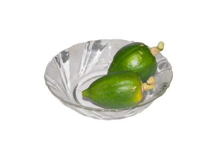 Small Green Papayas on a Glass Bowl isolated on white background photo