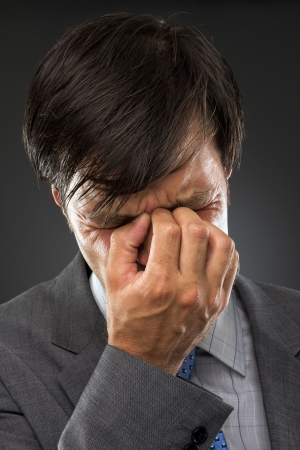 Closeup of young business man with headache rubbing temples Stock Photo - 15500883