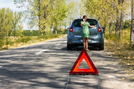 Woman calls to a service standing by a white car the focus is on the triangle Stock Photo