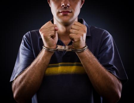 detenuti: uomo che indossa manette su sfondo nero Archivio Fotografico