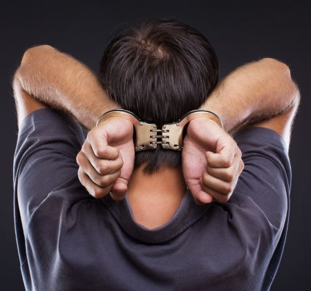 sequestration: Man in handcuffs with hands on neck on gray background