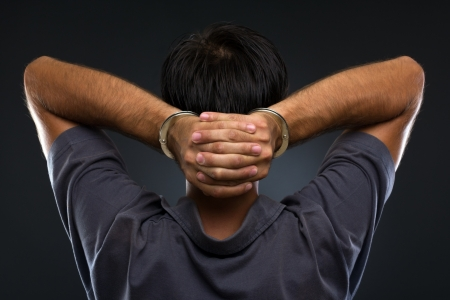 confiscation: Man in handcuffs with hands on neck on gray background