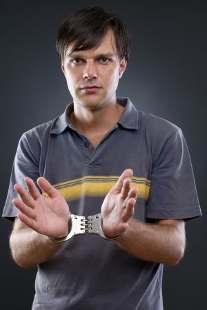 handcuffed man on gray backing Stock Photo - 15502236