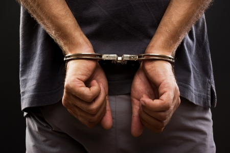 criminals: Close-up  Arrested man handcuffed hands at the back