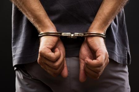 justiz: Close-up verhaftet Mann mit Handschellen gefesselten H�nde auf der R�ckseite