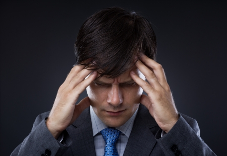 Closeup of young business man with headache rubbing temples Stock Photo - 15502235