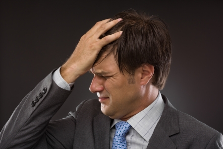 Closeup of young business man with headache on gray Stock Photo - 15502237