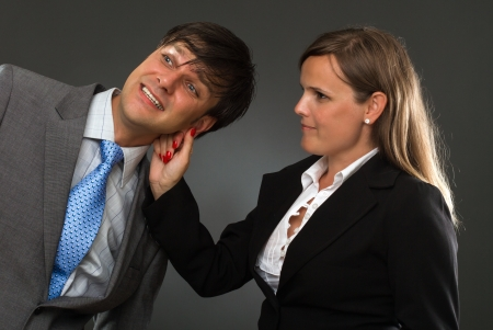 a hand pulling a businessman ear on gray photo
