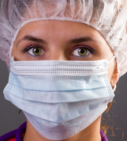 Portrait of a woman doctor wearing mask and cap - on grey background