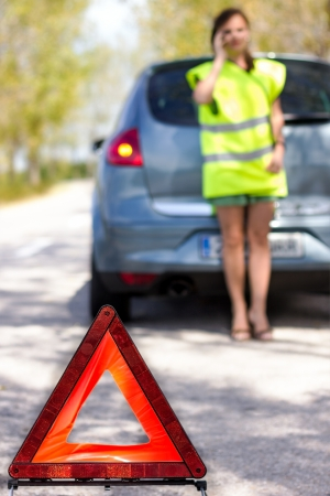 Red warning triangle with a broken down car photo