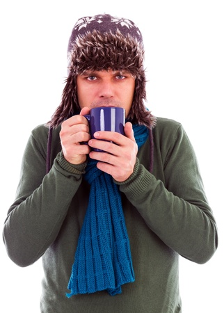 Young man with scarf warming up with hot drink in wintertime