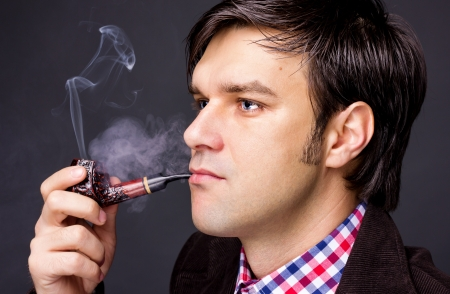 Closeup of a man smoking a pipe isolated on grey background Stock Photo