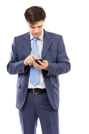 Portrait of a young businessman sending text messages against white background photo