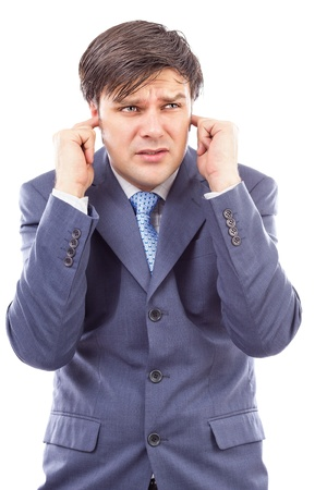 Young businessman with fingers in his ears  protecting himself from noise on white