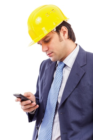 Portrait of a young engineer looking at his cellphone against white background photo