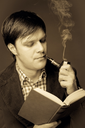 Portrait of a man reading and smoking a pipe. Close-up photo
