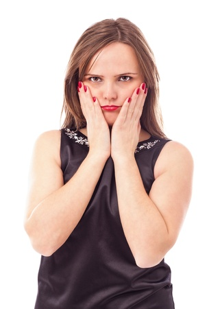 Portrait of a sulky young woman holding her face in hands against white background photo