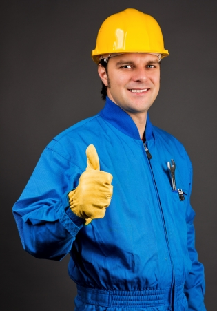 safety helmet: Young construction worker giving thumb up sign against gray Stock Photo