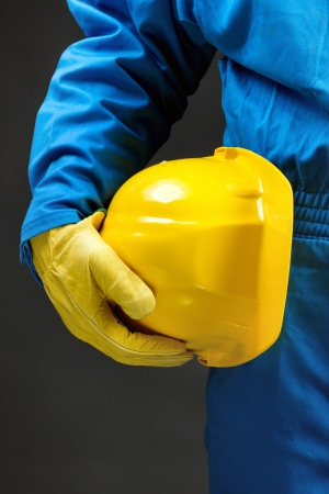 Yellow hardhat under arm. Part of body