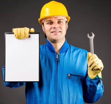 Portrait of a young worker holding a blank clipboard and a wrench on grey Stock Photo - 18499424
