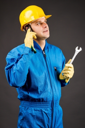 Young constuction worker speaking on phone and holding a wrench against gray Stock Photo - 18499491