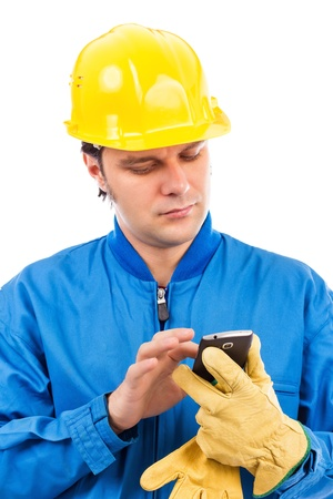 Portrait of a young construction worker using mobile phone isolated on white background photo