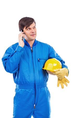 Portrait of a constuction worker talking on phone against white background photo
