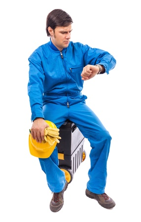 Worried construction worker looking at watch with serious expression on white Stock Photo - 18499300