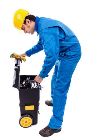 Young constuction worker looking through his toolbox against white background Stock Photo - 18499299