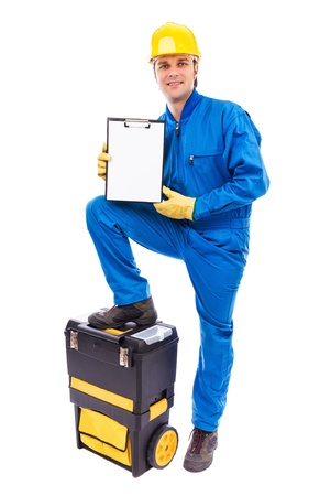 Young worker with a blank clipboard supporting his foot on his toolbox against white Stock Photo - 18499294