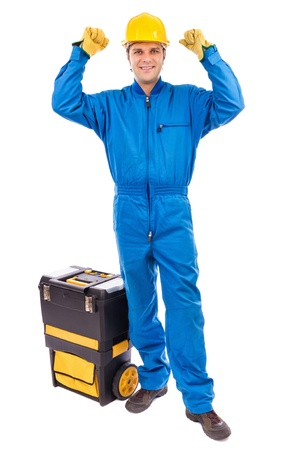Portrait of a young construction worker with his toolbox raising his arms in sign of victory against white  photo