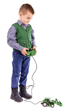 Portrait of a little boy playing with tractor toy  isolated on white background photo