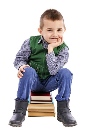 Cute little boy sitting on a pile of books smiling isolated on white.