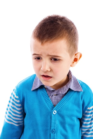 Closeup portrait of a disappointed cute little boy against white background photo