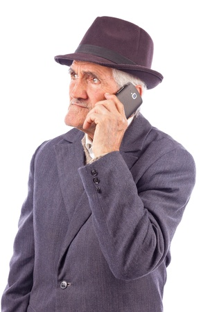 frowned: Portrait of an expressive senior talking on phone isolated on white background