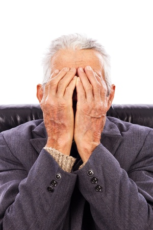 Senior man covering his face with both hands isolated on white background photo