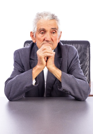 Portrait of a thoughtful elderly man holding his hands together under his chin  on white background photo